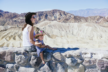 USA, California, Death Valley National Park, Twenty Mule Team Canyon, mother and baby girl sitting on wall - GEMF02846
