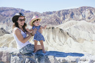 USA, California, Death Valley National Park, Twenty Mule Team Canyon, mother and baby girl on a wall - GEMF02849