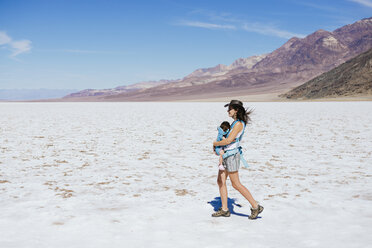 USA, California, Death Valley National Park, Badwater Basin, mother walking with baby girl in salt basin - GEMF02855