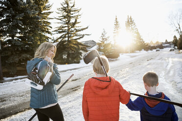 Mother and sons with ice hockey sticks and ice skates on sunny, snowy road - HEROF24367