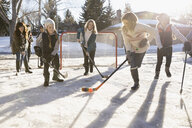 Mothers and daughters playing ice hockey in sunny, snowy driveway - HEROF24373