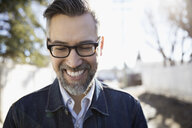 Happy mature hipster man looking down on sunny road - HEROF24376