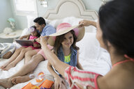 Mother and daughter trying on straw hat on bed - HEROF24436