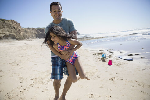 Latino father playing with daughter on sunny beach - HEROF24478