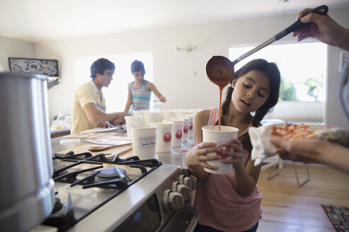 Mother and daughter cooking soup, pouring into container in kitchen - HEROF24490