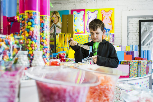 Boy buying various candies at shop - ASTF02841
