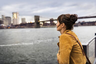 Side view of woman looking at East River while standing against Brooklyn bridge - ASTF02844