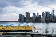 View of basketball court against East River and buildings against cloudy sky - ASTF02847