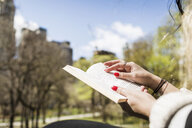 Cropped image of woman reading book at Central Park - ASTF02865