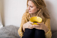 Thoughtful woman holding coffee cup while sitting on bed - ASTF02892