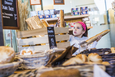 Cute girl buying breads in supermarket - ASTF03213