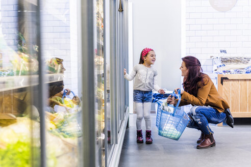 Happy mother and daughter at refrigerated section in supermarket - ASTF03216