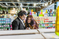 Couple shopping while standing in supermarket - ASTF03228