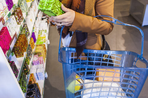 Midsection of woman carrying shopping basket in supermarket - ASTF03234