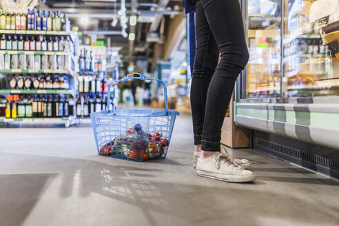 Low section of young man standing by shopping basket in supermarket - ASTF03237