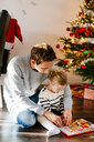 Father assisting daughter with game at home during Christmas - ASTF03270