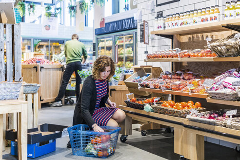 Young woman buying tomatoes while crouching in supermarket - ASTF03327