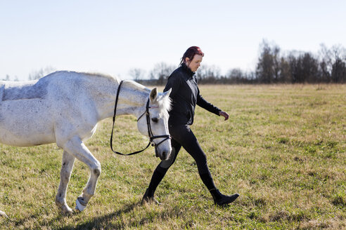 Side view of woman walking with horse on field - ASTF03363