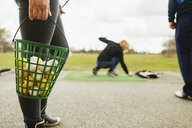 Low section of woman holding basket with balls at golf course - ASTF03378