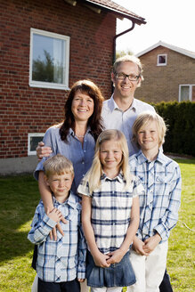 Portrait of family standing in back yard against house - ASTF03435