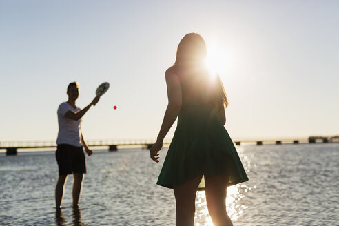 Couple playing tennis at shore against clear sky during sunset - ASTF03597