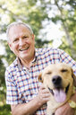 Portrait of happy senior man with dog against trees - ASTF03606