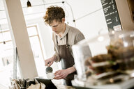 Young barista making cappuccino in coffee shop - ASTF03645