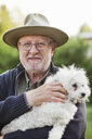 Portrait of smiling senior man wearing hat while carrying white dog at park - ASTF03786