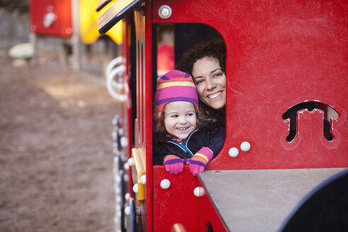 Portrait of happy woman with daughter enjoying at playground in park - ASTF03876