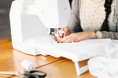 Midsection of design professional using sewing machine at table in studio - ASTF03888