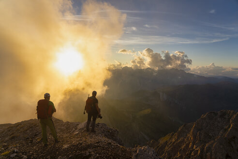 Italy, Veneto, Dolomites, Alta Via Bepi Zac, mountaineers standing in mountainscape at sunset - LOMF00822