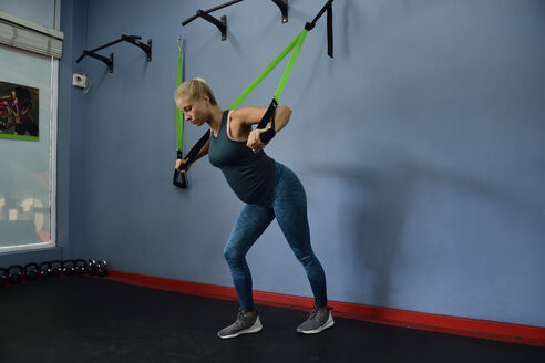 Pregnant woman doing suspension training in gym - ECP00517