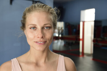 Portrait of smiling young blond woman in a gym - ECPF00523