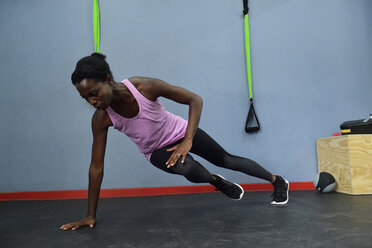 Woman practicing in a gym doing a side plank - ECPF00532