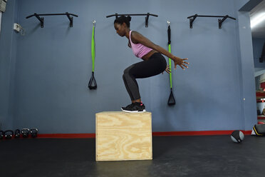 Woman practicing in a gym doing a box jump - ECPF00535