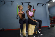 Two happy women doing fitness exercises with dumbbells in a gym - ECPF00538