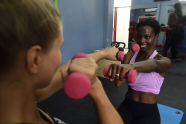 Two women doing fitness exercises with dumbbells in a gym - ECPF00544