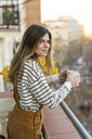 Portrait of relaxed young woman standing on balcony with cup of coffee - AFVF02390