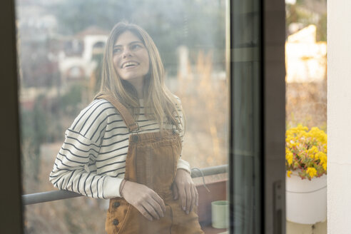 Portrait of smiling young woman relaxing on balcony - AFVF02393