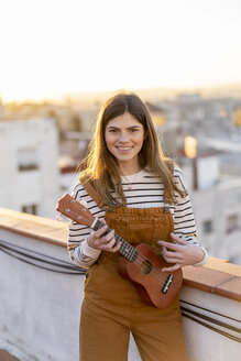 Portrait of smiling young woman standing on roof terrace in the evening playing ukulele - AFVF02399