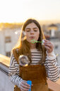 Portrait of young woman blowing soap bubbles on roof terrace in the evening - AFVF02402