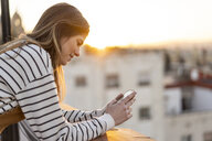 Young woman on balcony at sunset using mobile phone - AFVF02420