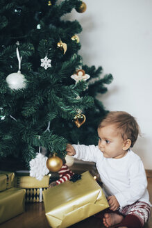 Baby girl sitting on the floor playing with Christmas decoration - MOMF00627
