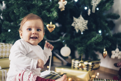 Portrait of smiling baby girl unpacking Christmas gifts - MOMF00630