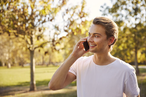 Young man on smartphone at a park - JHAF00034