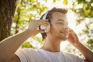 Smiling young man with headphones listening to music outside - JHAF00043