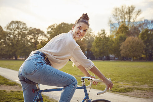 Young woman riding bike at a park - JHAF00046