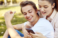 Young couple looking at smartphone at a park - JHAF00067