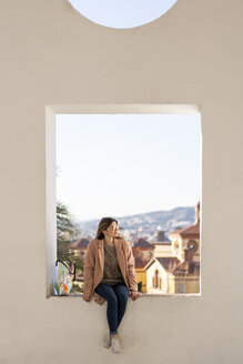 Young woman sitting on a wall looking sideways - AFVF02425