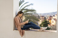 Laughing young woman sitting on a wall using cell phone - AFVF02428